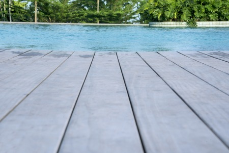 Closeup of wooden floor of swimming pool at the tropical resort with tropical trees background 免版税图像