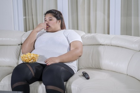 Picture of bored fat woman watching television while eating popcorn on the couch Foto de archivo