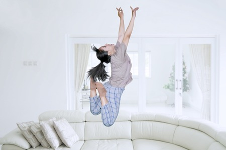 Picture of a young woman jumping in the living room with happiness expression