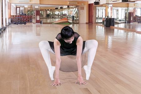 Image of beautiful ballet dancer doing stretches in the fitness center