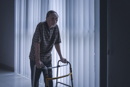 Portrait of lonely old man walking near the window with a walker at home