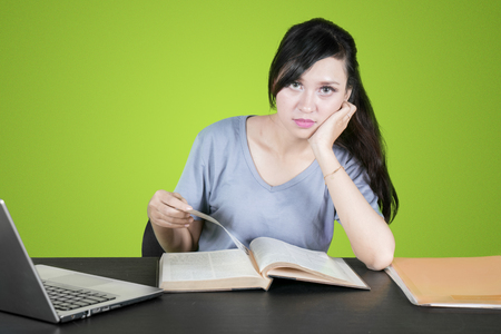 Beautiful female college student reading a book on the table and staring at the camera. Shot with green screen background
