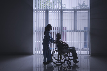 Silhouette of female nurse pushing her elderly patient in a wheelchair while walking near the window Zdjęcie Seryjne - 111289055