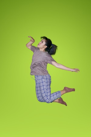 Casual female dancer jumping in the studio with green screen background