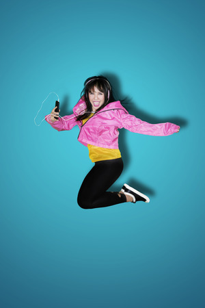 Joyful young woman listening to music with a mobile phone while jumping in the studio