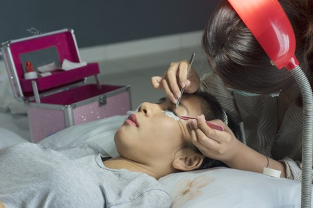 Picture of Asian woman eyes during eyelash extension treatment in a beauty salon Standard-Bild