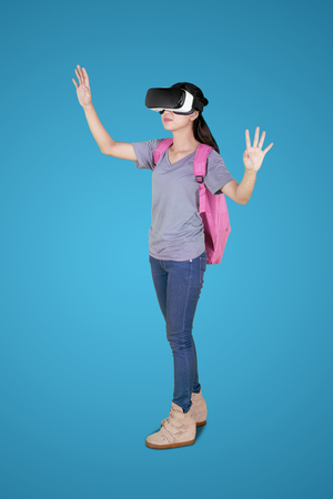 Full length of female college student using a virtual reality goggles while standing in the studio Stock Photo