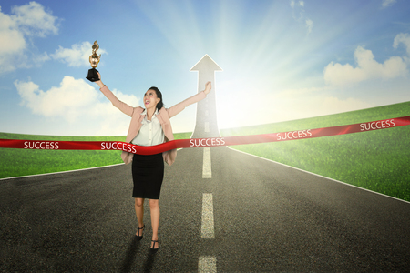 Happy business woman carrying a trophy while crossing the success line with upward arrow in the road