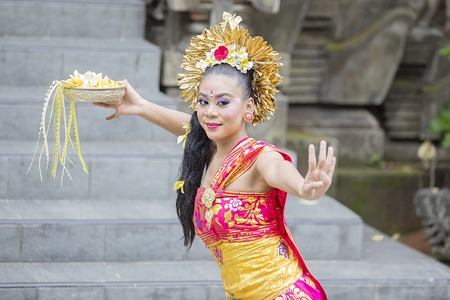 Picture of Balinese woman dancer dancing with graceful poses in the temple