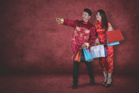 Chinese New Year Concept. Young Asian man pointing something in the studio after buying gifts with his wife