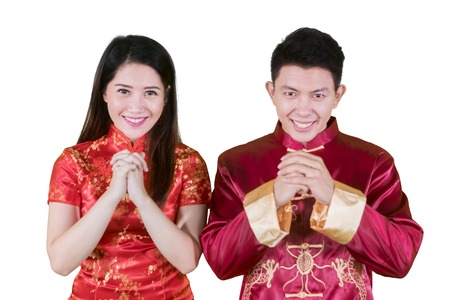 Picture of happy Chinese couple wearing cheongsam dress while congratulating Chinese new year in the studio