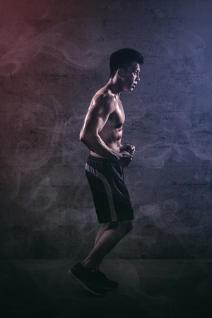 Side view of a muscular young man doing run exercises in the studio