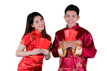 Picture of a young Chinese couple wearing cheongsam clothes and holding envelopes in the studio, isolated on white background 版權商用圖片