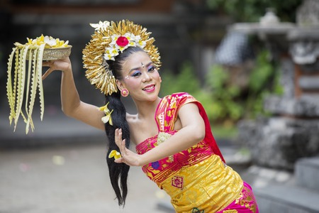 Asian female dancer wearing traditional dress costume while doing Pendet dances in the temple