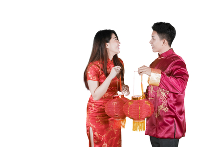 Picture of happy Asian couple carrying red lantern at Chinese new year in the studio, isolated on white background Stock Photo
