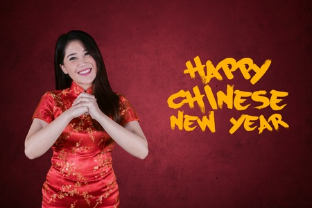 Happy woman congratulating to you while standing with text of Chinese new year in red background Stock Photo - 112461365