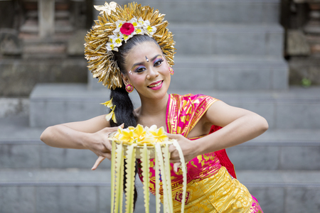 Female dancer smiling at the camera while doing Pendet dances in the temple Stockfoto