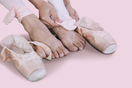 Close up of young female dancer taking off ballet shoes after dancing in the studio Foto de archivo