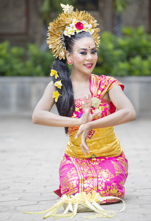 Image of pretty female dancer wearing traditional Balinese dress while performing Pendet dances at outdoor