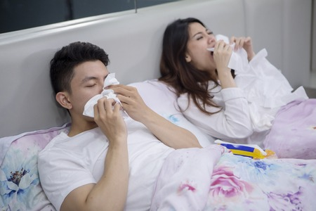 Portrait of sick Asian couple sneezing with tissues in their hands while lying in the bed Stok Fotoğraf