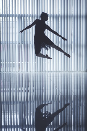 Silhouette of beautiful ballerina jumping and dancing near the window