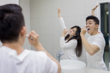Portrait of happy young couple brushing teeth in the bathroom while dancing front a mirror Stock fotó