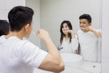 Picture of Asian couple brushing teeth in the bathroom while looking at mirror Stockfoto