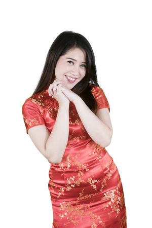 Portrait of happy woman wearing traditional cheongsam dress and congratulate happy Chinese new year in the studio