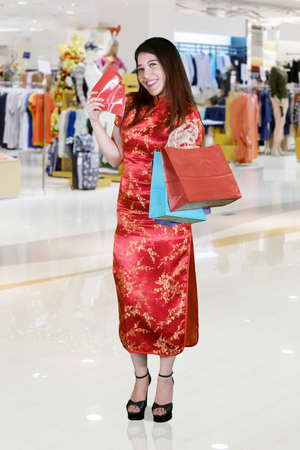 Full length of cheerful woman holding red envelopes after shopping in the mall. Chinese New Year Concept