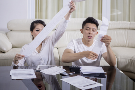 Image of young couple calculating their expenses and holding paper at home