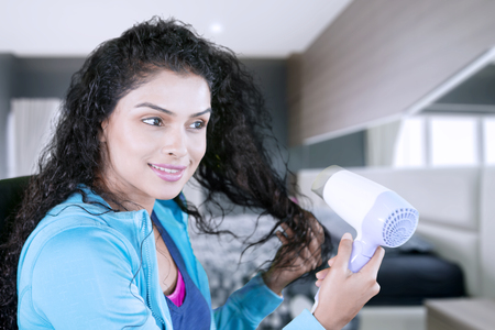 Portrait of young Indian woman using a hair dryer while sitting in the bedroom