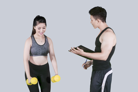 Image of pretty girl assisted by her trainer while doing exercise with dumbbells in the studio