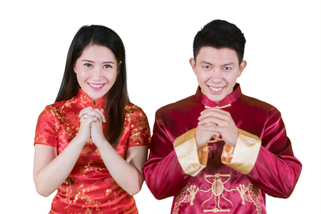 Asian couple congratulates happy Chinese new year while wearing cheongsam dress, isolated on white background Stock Photo