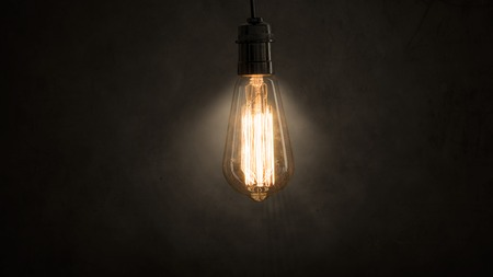Image of an incandescent light bulb glowing in dark room Фото со стока