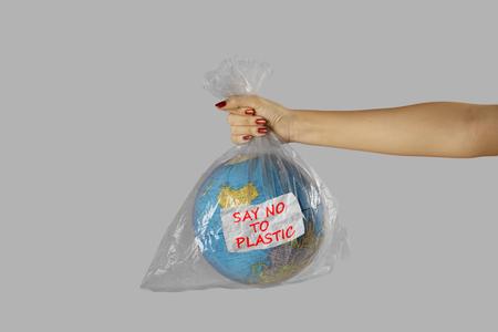 Concetto di Giornata mondiale dell'ambiente. Donna sconosciuta in possesso di una plastica con globo mondiale e testo di dire no alla plastica Archivio Fotografico