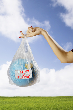 Close up of female holds an earth globe in a plastic bag with text of say no to plastic. Shot in the meadow