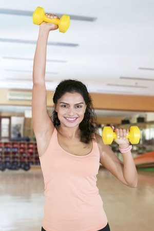 Picture of curly hair woman smiling at the camera while lifting two dumbbells in the fitness center