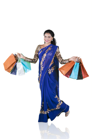 Happy Indian woman holding shopping bags and smiling at the camera while wearing saree clothes. Isolated on white background