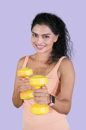 Portrait of pretty girl exercising her biceps with dumbbells in the studio with purple background 写真素材