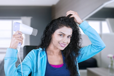 Image of beautiful woman drying her wet hair with a hair dryer while sitting in the bedroom
