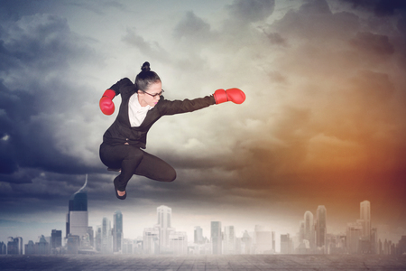 Picture of Asian female entrepreneur wearing boxing gloves while jumping and punching through at outdoor