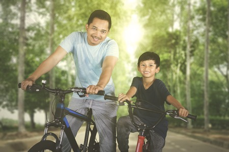 Picture of young father smiling at the camera while riding bicycle  with his son in the park Reklamní fotografie