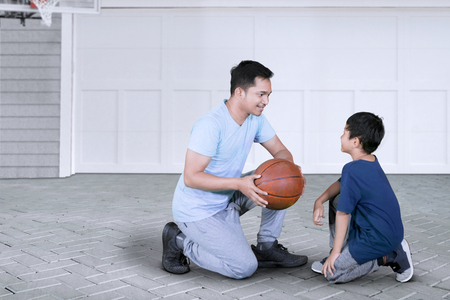 Picture of young man kneeling in the garage while teaching his son to play basketball