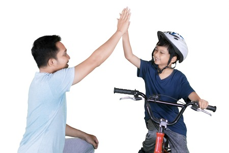 Picture of Asian little boy riding bicycle while giving high five hands with his father in the studio Stock Photo