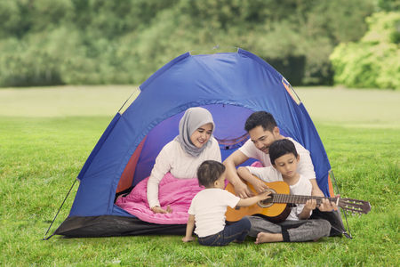 Picture of young family playing a guitar while enjoying their holiday in the campground Foto de archivo