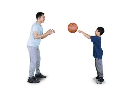 Picture of happy little boy passing a ball to his father while doing basketball exercises in the studio