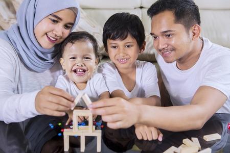 Bild einer glücklichen Familie, die mit Holzblöcken spielt, um ein Traumhaus zu bauen, während sie im Wohnzimmer sitzt