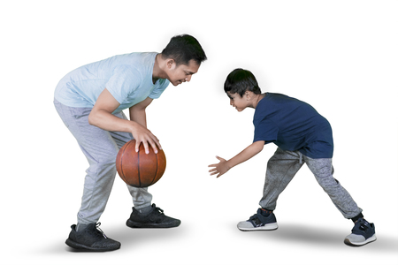 Picture of a young man playing basketball with his son while exercising in the studio, isolated on white background