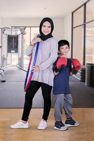 Portrait of young mother holding a  hoop while standing with her son in the gym center
