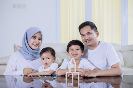 Picture of young family sitting in the living room while playing with wood blocks to build a dream house